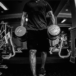 Black and white image of a man walking with 90 lb. dumbbells in each hand.
