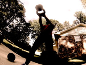 A an image of a female athlete swinging a kettlebell from a ground view.