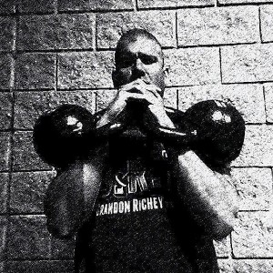 Black and white image of Brandon holding a pair of kettlebells in the rack position.