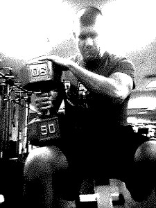 Black and white image of Brandon sitting with a 90 lb. dumbbell on knee preparing to press it.