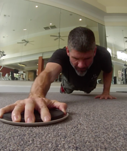 Brandon demonstrating mobility with a glide disc push up sliding the disc in his right hand.