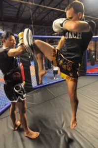 A Thai fighter jumping up to strike a Thai pad by performing a flying knee strike after MMA strength and conditioning.