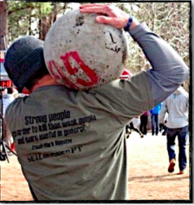 Man carrying an atlas stone on his shoulder displaying functional fitness