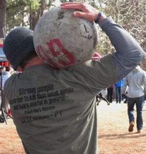 A man with his back to the camera wearing a long sleeve shirt holding an atlas stone on his right shoulder demonstrating functional fitness.