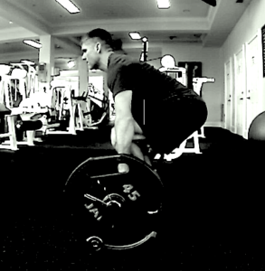 Black and white side view image of Brandon performing the barbell deadlift.