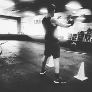 Brandon Richey Fitness strength student Dan is performing kettlebell swings with this back to the camera in a black and white image.