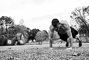 Black and white image of a muscular shirtless man performing push-ups in a field to the right of the frame.