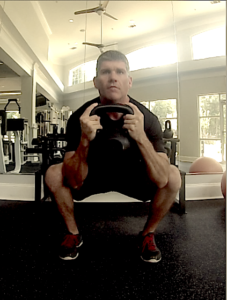 Brandon performing a goblet squat with a kettlebell facing the camera.