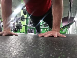 A picture taken from ground level looking at a man in the upright push-up position.