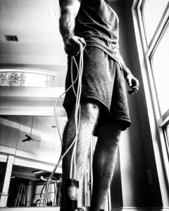 Black and white image of a man gripping the end of a jump rope with hand with it dangling by his side.