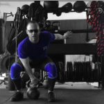 Man bending down to pick up a kettlebell for a clean and rack wearing a blue shirt and blue knee pads.