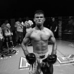 Black and white image of a Thai Boxer posing down the camera prior to a fight.