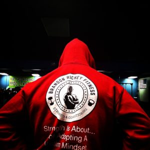 Brandon standing with his back to the camera displaying his sweatshirt with the Brandon Richey Fitness ghost man logo.