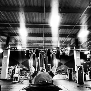 Black and white image of Brandon performing a set of heavy incline dumbbell bench press.