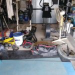 A garage gym cluttered with equipment ranging from sandbags to kettlebells.