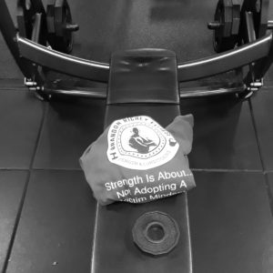 A black and white image of a bench press with the Brandon Richey Fitness hoodie folded at the center of the bench.