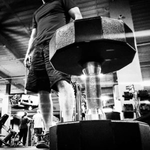 Black and white image of a dumbbell in the foreground of the image with a man standing in the background.