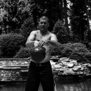 Black and white image of Brandon performing a single arm kettlebell swing and transitioning hands with the kettlebell during the movement.