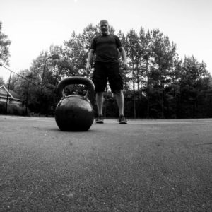 Black and white image with a kettlebell in the foreground and a man standing behind it in the distance.