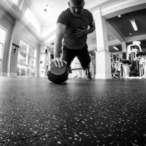 Black and white image of a man performing a one arm push-up off of the kettlebell.