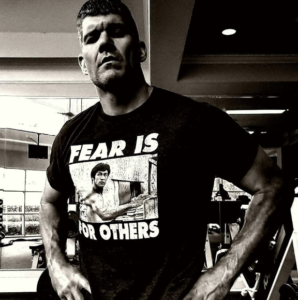 Black and white image of Brandon wearing a Bruce Lee shirt standing with his hands on hips.