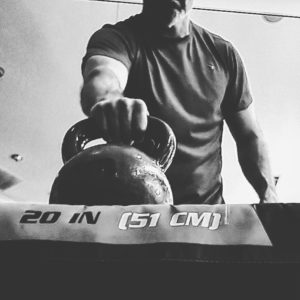 Black and white image of a man about to lift a kettlebell off of a box with his right arm.