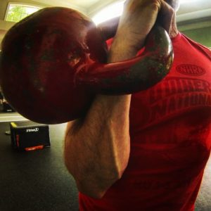 Man holding a big red kettlebell in the racked position with his right arm.