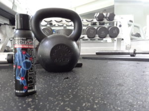 Bottle of CobraZol Sport setting on the ground in front of a kettlebell.